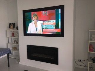 Wall Mounted TV above recessed gas fireplace by Jim's Antennas