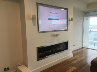 Gas log fire place with Wall Mounted TV above by Jim's Antennas