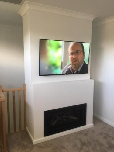 TV Mounted on Wall above Fireplace by Jim's Antennas