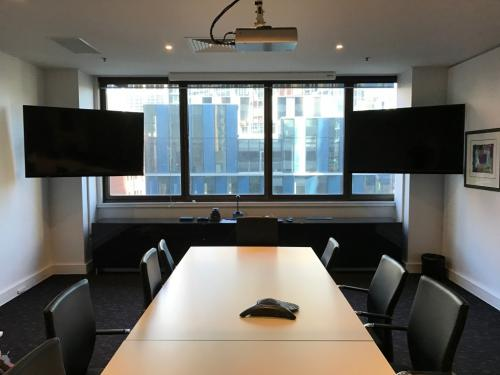 Dual screens mounted on movable arms in boardroom by Jim's Antennas